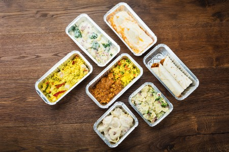 77052517 - different type of ready tasty meals in foil containers on the table